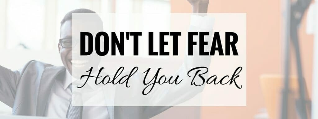 "Gentleman smiling with arms in the air in achievement. Text ""Don't let fear hold you back"" super-imposed over image."