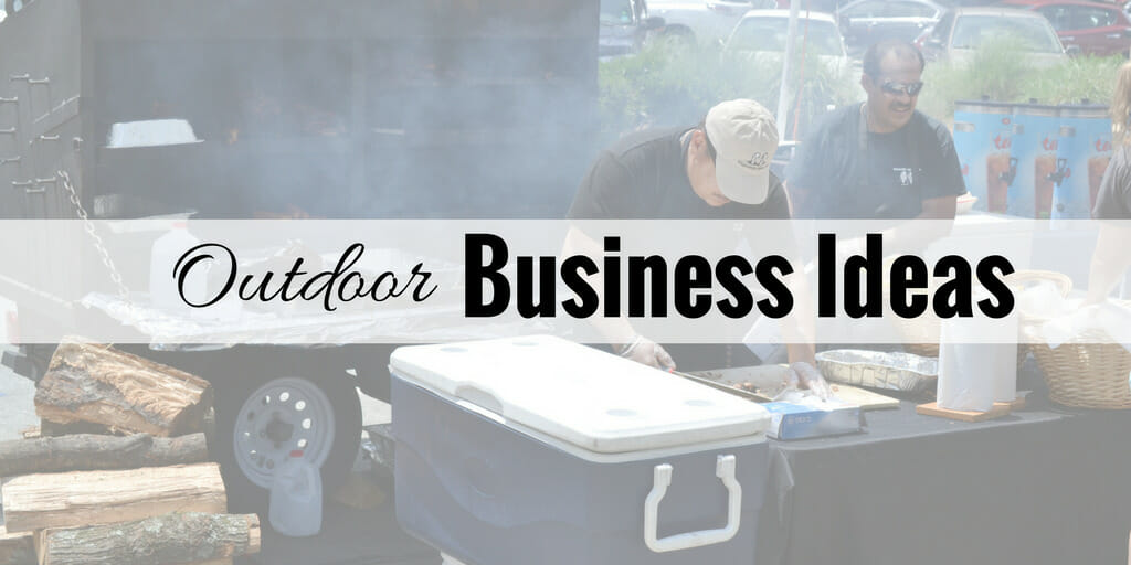 two men working on food preparation outside with smoker in background smoking food.